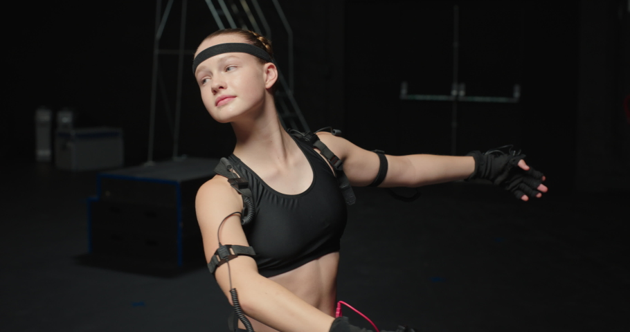 Dancing woman wearing motion capture suit in studio ballet dancer girl wearing mo-cap suit for 3d character animation for virtual reality technology | Shutterstock HD Video #1061018617