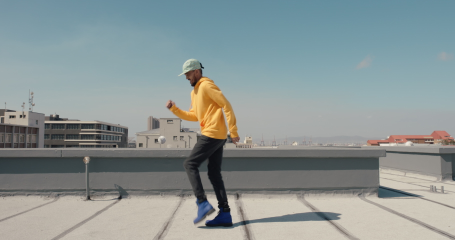 Dancing man hip hop dancer performing freestyle dance moves on rooftop in city wearing yellow hoodie | Shutterstock HD Video #1061018749