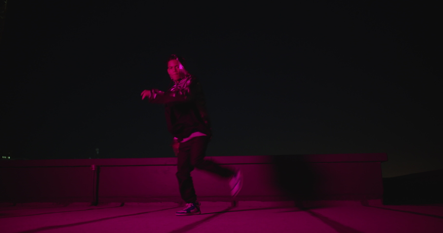 Dancing man breakdancing on rooftop at night hip hop dancer practicing dance routine performing freestyle moves in city with red light | Shutterstock HD Video #1061018791