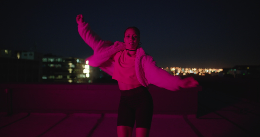Happy woman dancing on roof top girl performing hip hop dance style having fun freestyle dancer in urban city at night with red light | Shutterstock HD Video #1061018800