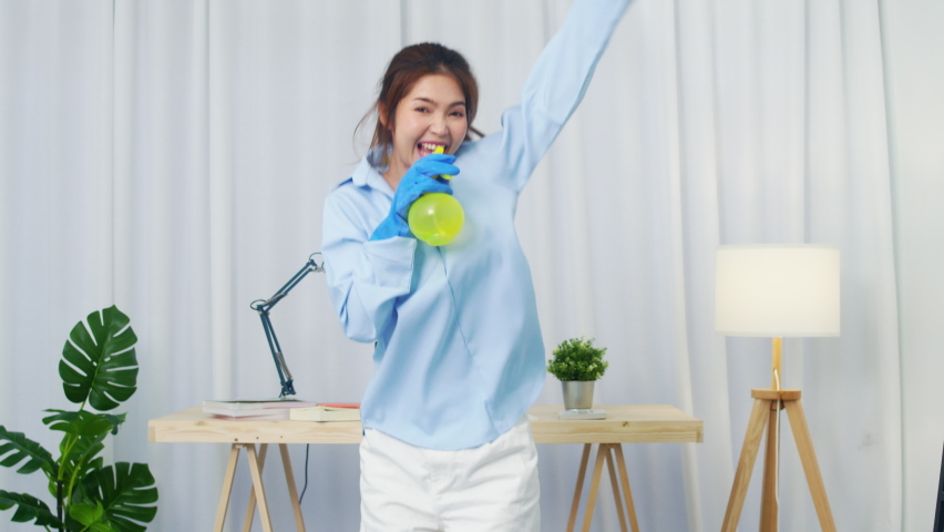 Funny happy young Asia woman holding spray microphone singing song music in modern living room while doing housekeeping in the house. Lifestyle women at home concept. Slow motion shot. | Shutterstock HD Video #1061020690