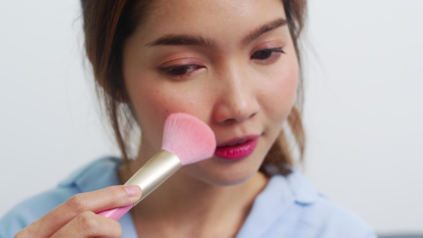 Asian woman using powder by brush make up in front mirror, Happy female using beauty cosmetics to improve herself ready to working in bedroom at home. Lifestyle women at home concept | Shutterstock HD Video #1061020693