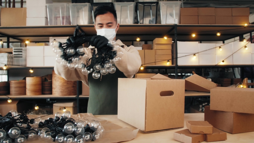 Asian craftsman man making light bulb garland, manufacturing, christmas decoration factory, chinese male in medical mask making home decor lantern, business reopen after covid coronavirus pandemic | Shutterstock HD Video #1061021440