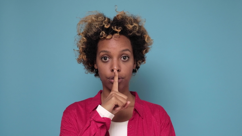 Pretty young African American woman makes silence gesture, presses index finger to lips. Slilence please. Strict female makes hush sign | Shutterstock HD Video #1061026789