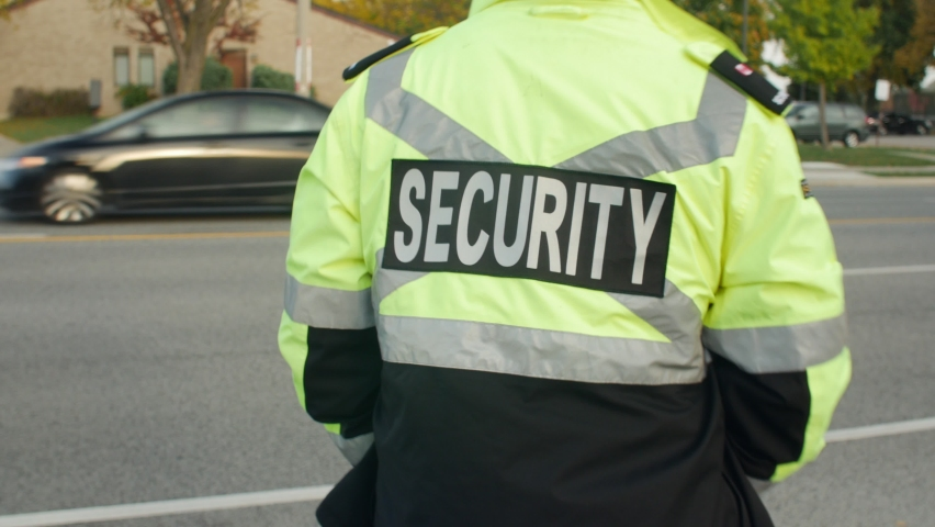 Security guard patrolling street next to highway Royalty-Free Stock Footage #1061027689