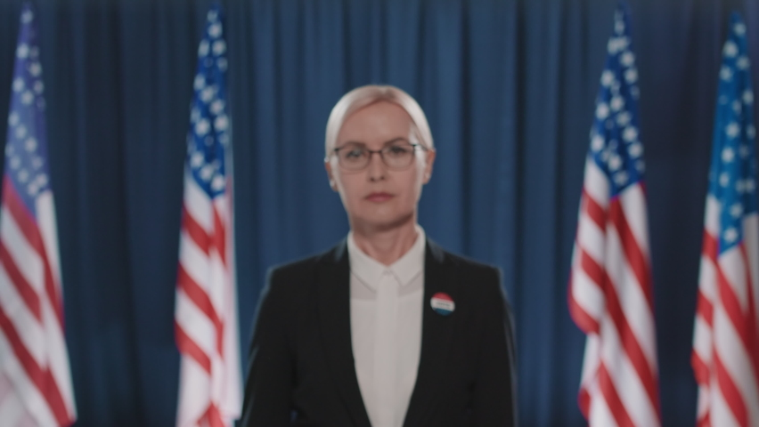 Medium close-up portrait shot footage of mature Caucasian woman wearing eyeglasses taking part in presidential elections looking at camera