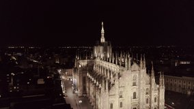 Aerial drone footage of famous statue on cathedral Duomo in Milan Italy by night // no video editing