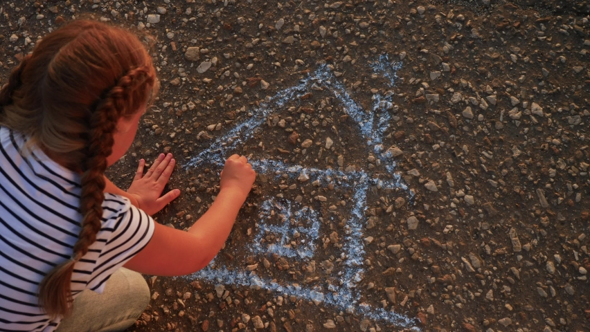 Child kid draw a house on the asphalt with chalk . childhood mortgage dream kid concept. little girl playing draws with chalk big house. concept loan mortgage for a dream home residential building