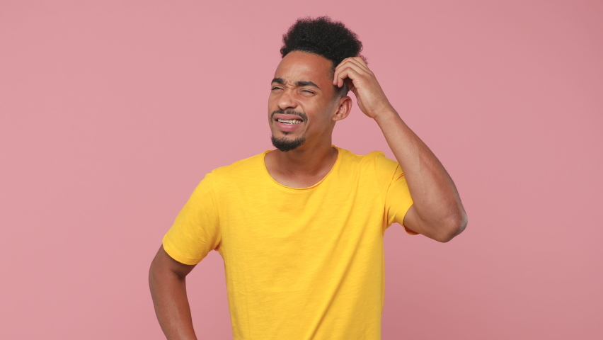 Preoccupied excited young african american man in yellow t-shirt posing isolated on pink background in studio. People lifestyle concept. Put hand on head holding index finger up with great new idea Royalty-Free Stock Footage #1061042623