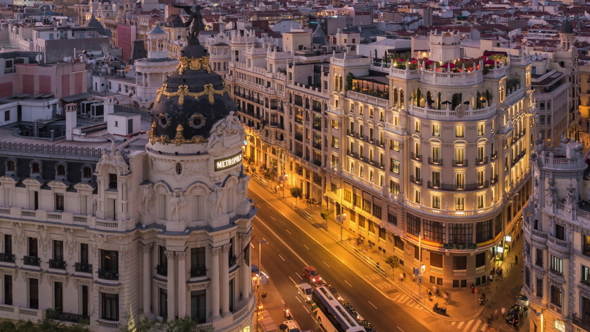 Zoom out time lapse view of sunset over historic buildings and traffic on Gran Via street in Madrid, the capital and largest city in Spain.