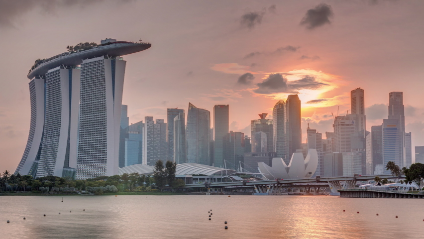 Sunset over the downtown skyline of Singapore as viewed from across the water from The Garden East timelapse. Sun behind skyscrapers. Singapore. Reflection in water Royalty-Free Stock Footage #1061045641