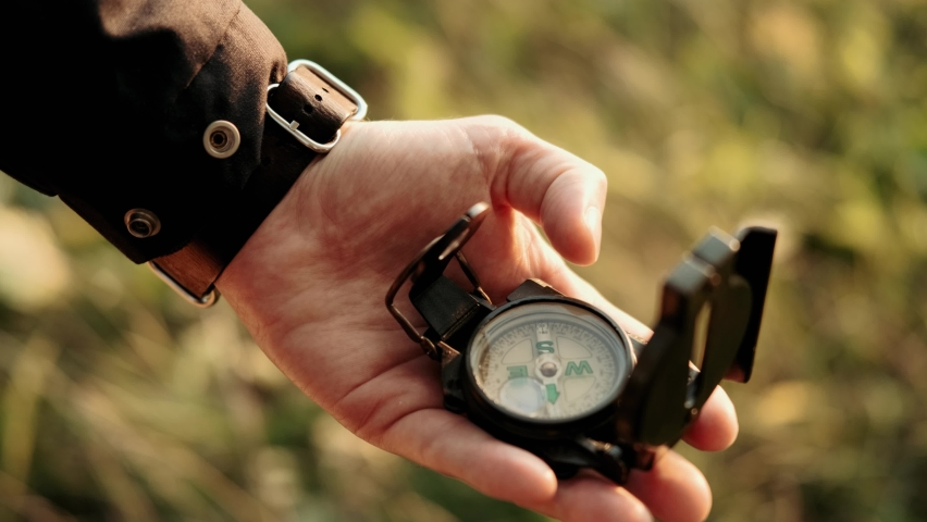 Man holds a compass in hand and looks for direction. Active lifestyle hiking enjoying vacation travel tourism adventure landscape nature. Travelling. Hiking. Orienteering on terrain. | Shutterstock HD Video #1061050315