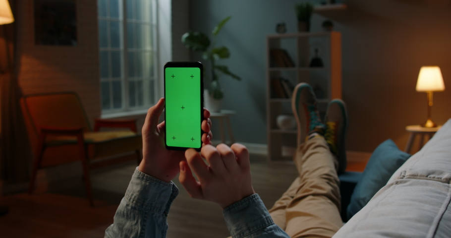 Close up shot of guy relaxing on couch at night, using smartphone with chroma key green screen and doing various gestures on display - technology, communications concept 4k template   Shutterstock HD Video #1061053939