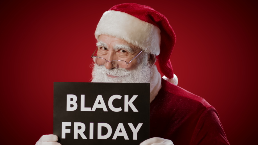Lockdown of smiling Santa Claus standing against red wall, holding lettering Black Friday and looking at camera Royalty-Free Stock Footage #1061064157