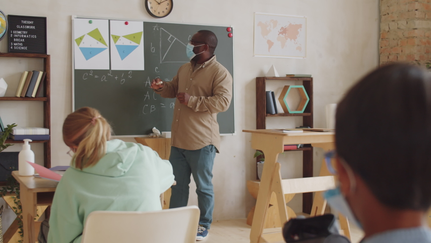 A male teacher in protective face mask standing by chalkboard in front of children in the classroom. pointing at posters and explaining math lesson while working in school during covid-19 outbreak. Royalty-Free Stock Footage #1061067148