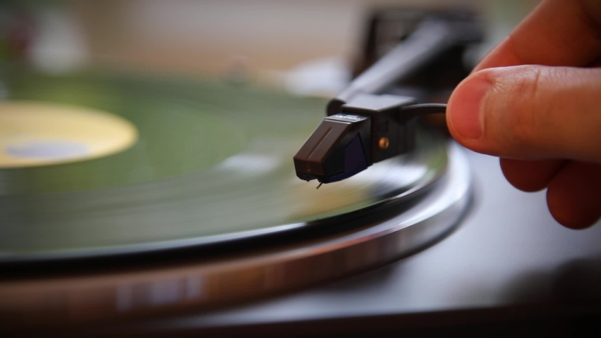 Hand turns on a vintage vinyl record. The needle rises from a vintage vinyl record. The vinyl record is spinning. The needle plays on a vintage vinyl record. Old turntable. Royalty-Free Stock Footage #1061069224