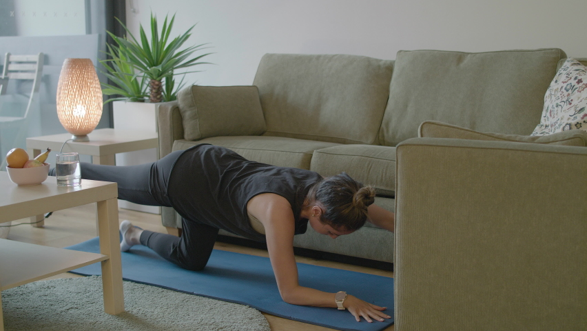 Women kicks over table lamp while trying to work out in her cluttered living room.