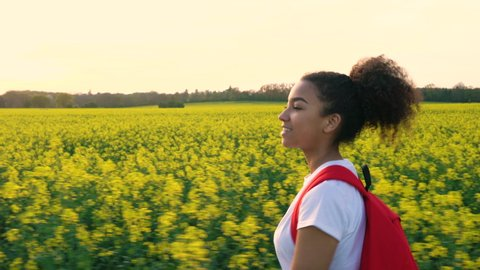Tracking shot of a beautiful happy mixed race African American girl teenager female young woman walking or hiking with red backpack on path through field of yellow flowers