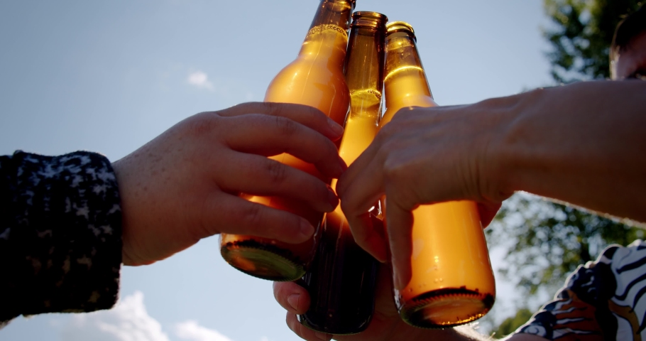 Celebration beer cheers concept, hands holding up bottles of beer of people group in outdoor party vacation. Close up. Slow motion V3 Royalty-Free Stock Footage #1061082253