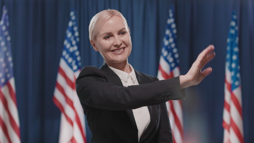 Medium portrait shot of cheerful Caucasian woman running for USA presidency waving hand to voters