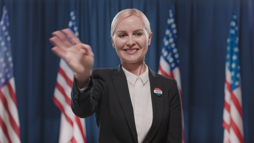 Medium portrait shot footage of mature Caucasian female candidate running for USA presidency waving hand to electorate