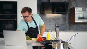 Young man watching video recipe on laptop while cooking vegetables in kitchen. Portrait of handsome guy in apron and glasses learning how to cook watching webinar on computer at home kitchen