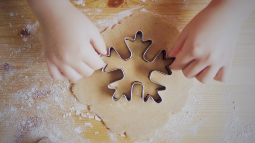 Close-up top view of a child's hand making a gingerbread cookie in the form of a snowflake. Christmas and New Year concept Royalty-Free Stock Footage #1061086243