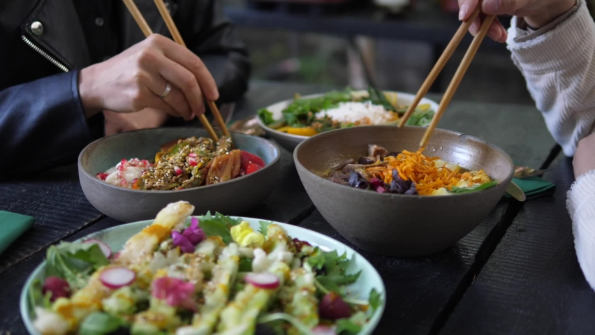 Healthy Asian vegan lunch served in rustic cafe. Two people eating their healthy vegan meals with chopsticks. Royalty-Free Stock Footage #1061098231