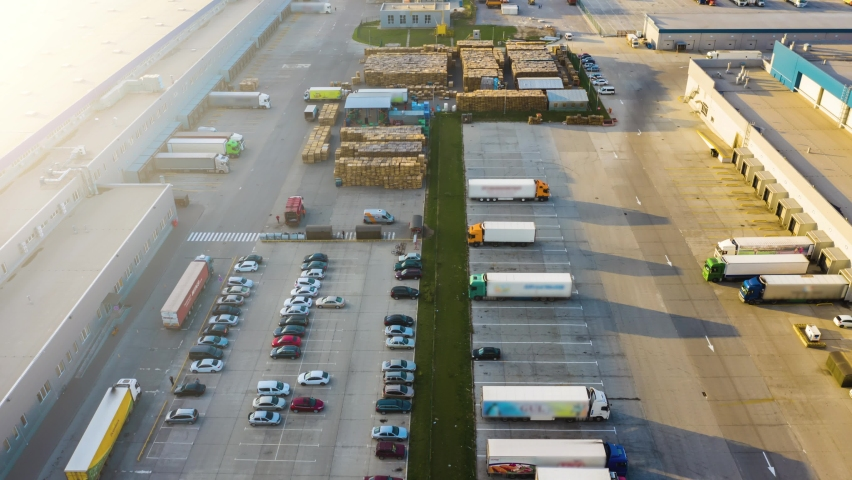 Logistics park with a warehouse - loading hub. Semi-trucks with freight trailers standing at the ramps for loading/unloading goods. Aerial hyper lapse - motion time lapse Royalty-Free Stock Footage #1061100376