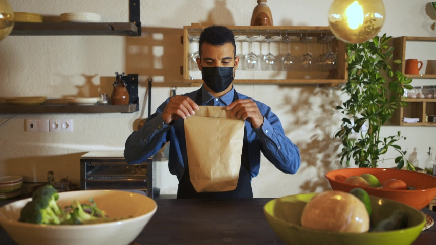 African american waiter wearing protective face mask giving bag to customer at counter bar. Young man worker working with take away orders during corona virus outbreak. Concept food & drinks takeaway Royalty-Free Stock Footage #1061100700