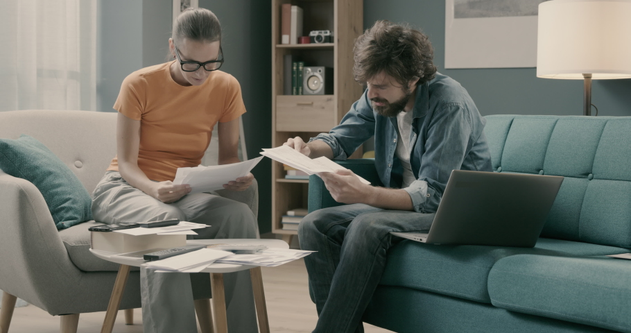 Stressed young couple managing their finances at home and checking bills, they have budgeting problems | Shutterstock HD Video #1061101423