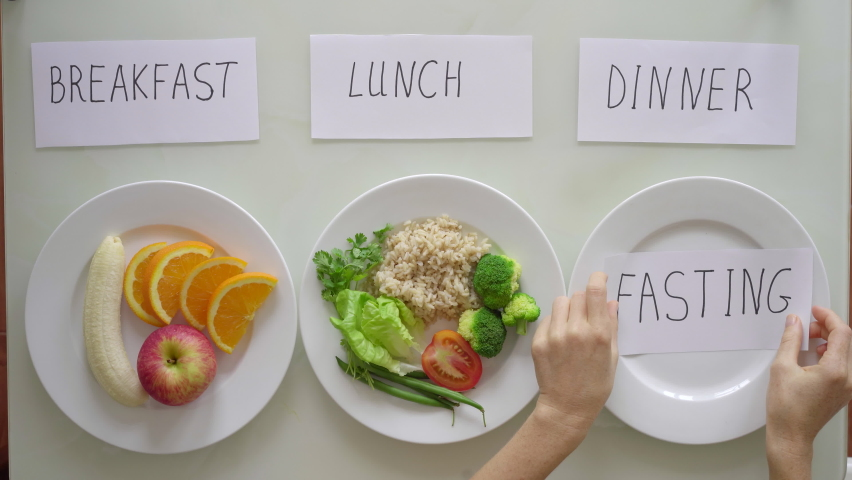 Hands of a woman put a plate with cut fresh fruits and brown rice with vegetables under the titles breakfast and lunch respectively, after which under the title dinner she puts empty plate with title