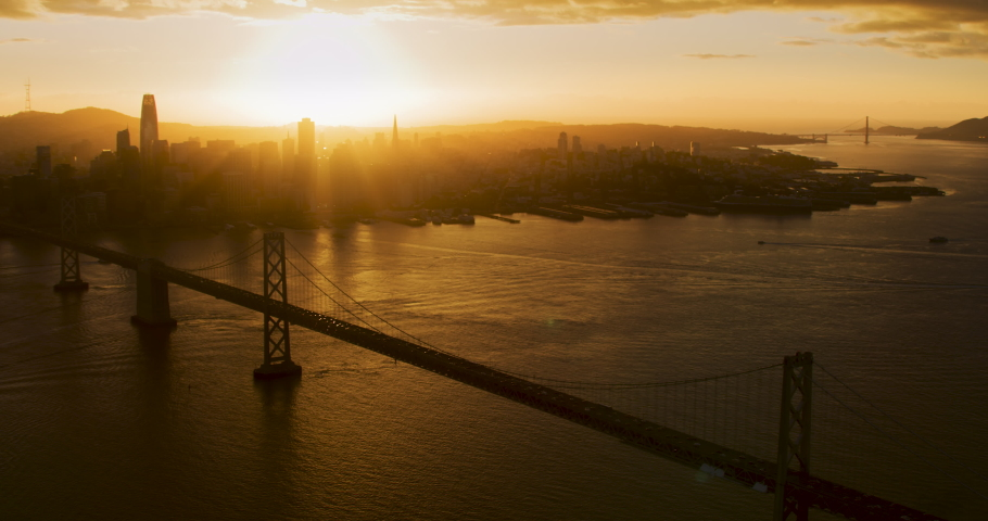 Aerial view of the Oakland bay bridge during sunset. Backlight. San Francisco, California. United States. City skyline in the background. Shot on Red weapon 8K.