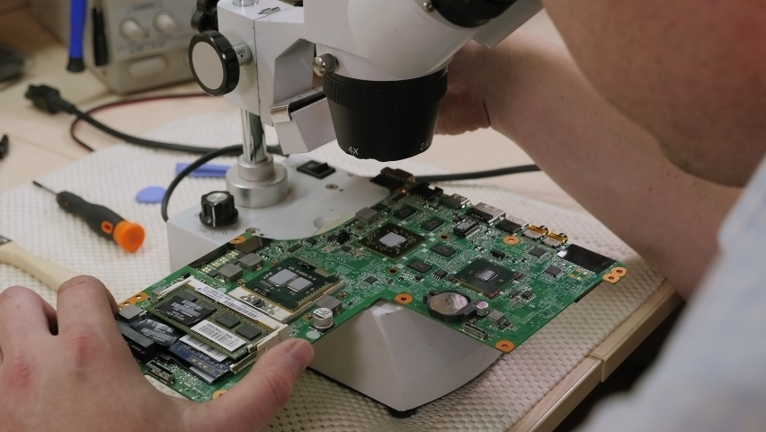 Young man repairing computer components in service center with the help of a Microscope. Electronics repair service concept. Royalty-Free Stock Footage #1061123692