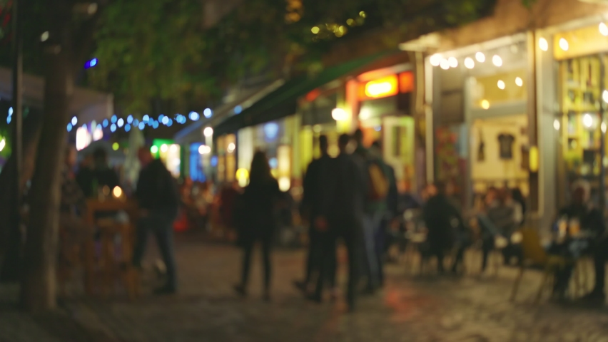 Evening street in the old town with numerous cafes and restaurants. People chat, eat and drink while sitting at cafe tables on summer terraces. Evening city illumination and comfort. Blurred out