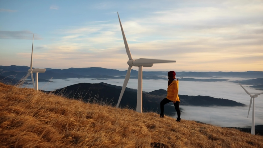 Epic shot of a woman hiking on the edge of the mountain against landscape with wind turbine power station on background. Concept of environmental engineering, renewable energy and love for nature. Royalty-Free Stock Footage #1061127232