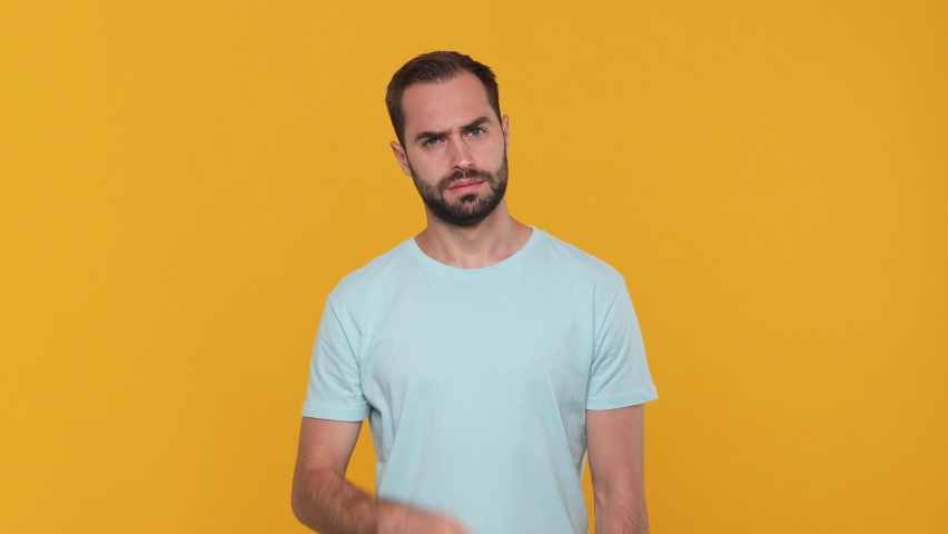 Bearded mysterious young man 20s in basic casual blue t-shirt isolated on yellow background studio. People emotions lifestyle concept. Looking camera say hush be quiet with finger on lips shhh gesture | Shutterstock HD Video #1061129932