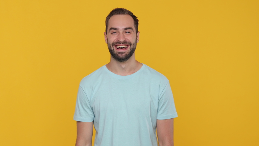 Bearded mysterious young man 20s in basic casual blue t-shirt isolated on yellow background studio. People emotions lifestyle concept. Looking camera say hush be quiet with finger on lips shhh gesture | Shutterstock HD Video #1061130040
