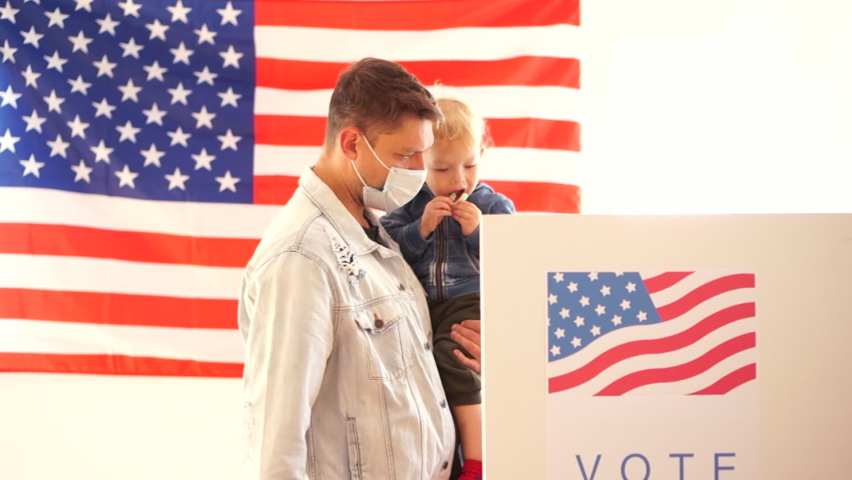 USA elections 2020 concept. Young man in a protective mask with a small child in his arms votes in a voting booth at a polling station
