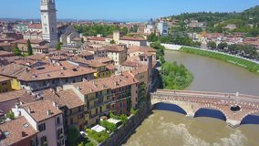 Panoramic aerial drone view of Verona, Italy. The drone approaches the river Adige, the typical Italian apartment rooftops and bridge Ponte Pietra. Video in 4K