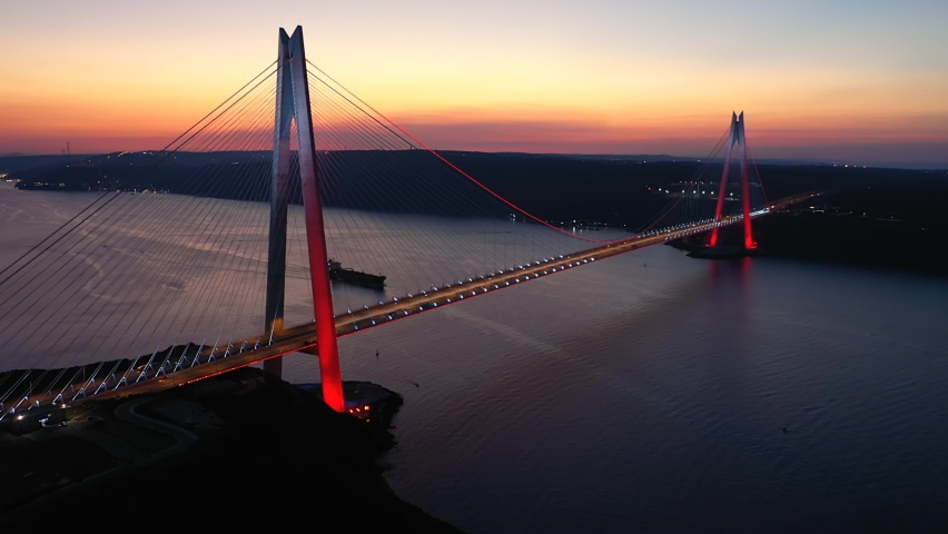 Istanbul Bosphorus at sunset. Yavuz Sultan Selim Bridge with the lights and red reflections in Sea. Bridge crosses the Bosphorus Strait between Garipçe village on the European side and Poyraz    Shutterstock HD Video #1061136172