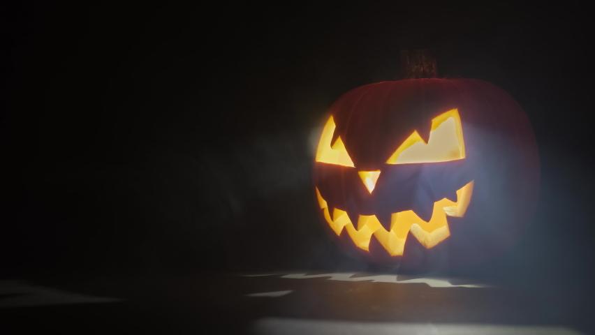 Halloween pumpkin with smoke at dark background. Pumpkin glows on Halloween night. Halloween concept with copy space. 4K, UHD | Shutterstock HD Video #1061136184