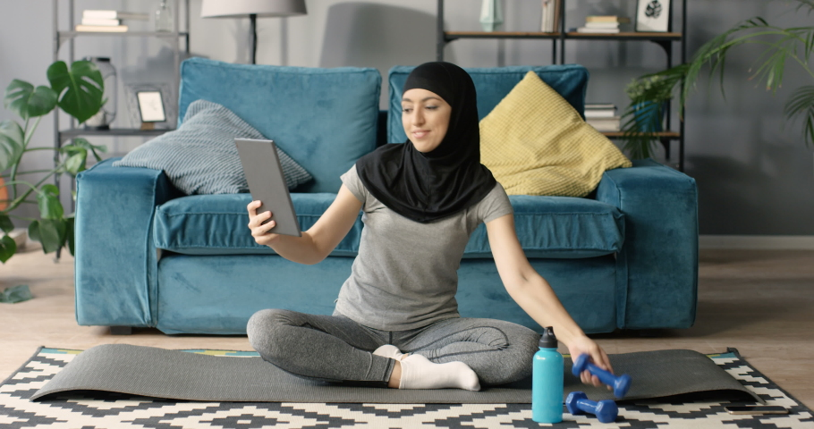 Muslim cheerful woman in hijab sitting on yoga mat on floor, exercising with dumbbell for strong arm biceps and videochatting on tablet device on webcam. Female Arab sport instructor online. Videochat Royalty-Free Stock Footage #1061140270