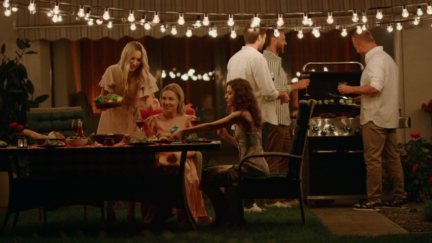 Cheerful friends enjoying barbeque party on backyard at evening. Handsome men preparing meat on grill. Attractive women talking at dining table near house. Young people spending time together outdoors