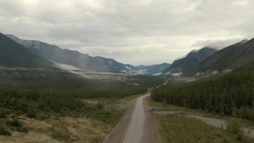 Picturesque View of Scenic Road from Above alongside Winding Glacial River. Aerial Drone Shot. Alaska Highway in the Northern Rockies, British Columbia, Canada.