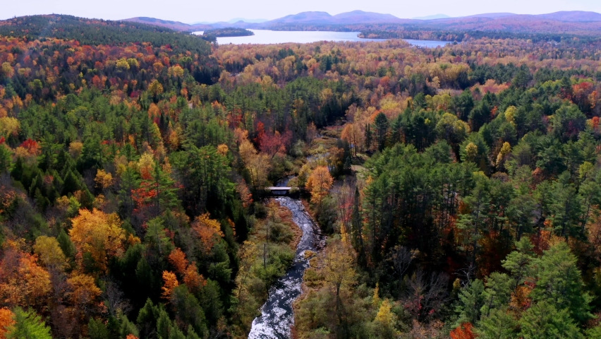 Aerial flythrough of Winding River Through Autumn Trees with Fall Colors in Adirondacks, New York, New England, USA | Shutterstock HD Video #1061148844