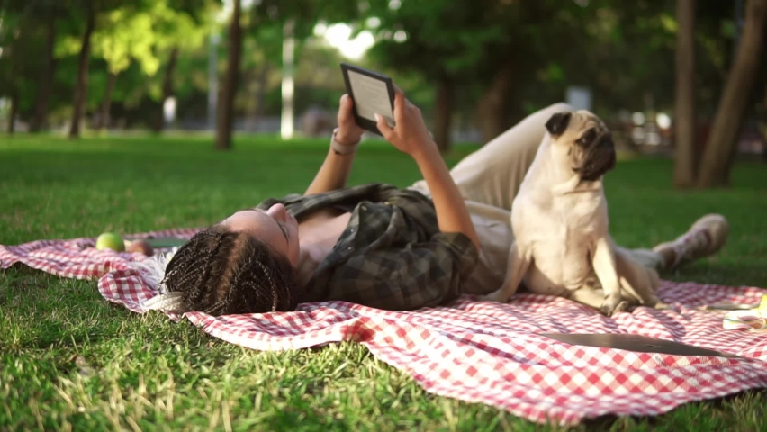 Woman laying on plaid on lawn in a park and reading e-book while little pug sitting next to her   Shutterstock HD Video #1061152006