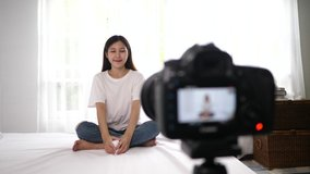 Selective focus, Teenager female is young blogger sitting on bed to review best product in her hand, sale online and record clip by camera, work at home concept