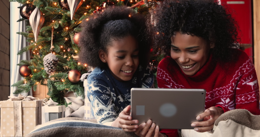 African mother and daughter spend holiday free time using tablet device choose gifts for family enjoy easy comfort remote shopping. E-commerce retail, Christmas sale, web store advertisement concept Royalty-Free Stock Footage #1061159641