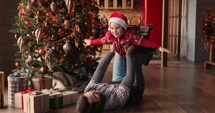 Father lying on warm wooden floor in living room decorated with lights glowing Christmas tree lift up small son wear Santa hat and sweater, family having fun play at home enjoy happy holidays concept Royalty-Free Stock Footage #1061161816